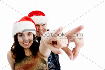 portrait of pointing couple with christmas hat