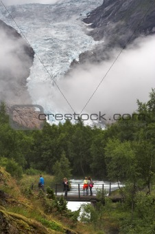 Tourists on the bridge over the stream at Briksdal glacier