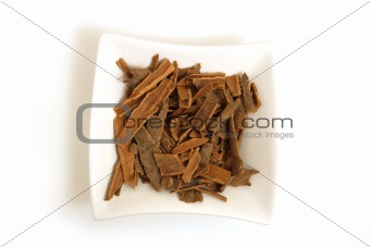 cinnamon in square white bowl isolated