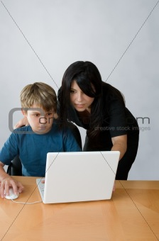 Adult assisting child on computer