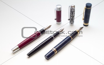 three pens with caps