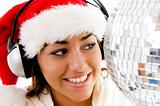 smiling young girl posing in christmas hat and listening to song