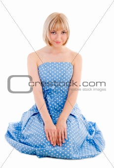 Sitting woman in blue polka dot dress