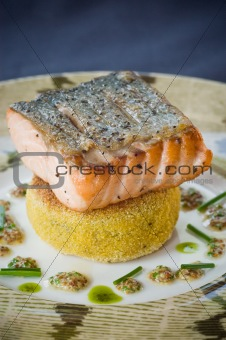 A seared Salmon fillet nicely placed on a Polenta fritter