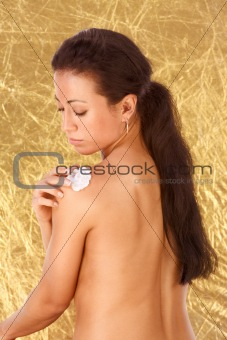 Ethnic woman applying moisturizer on her shoulder