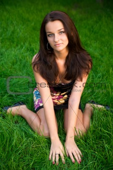 Beautiful young brunette sits on the green grass
