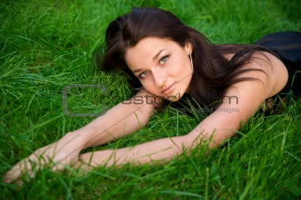 Beautiful young brunette rests on the green grass