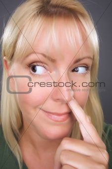 Blond Woman with Finger in Her Nose Against a Grey Background.