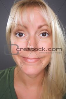 Beautiful Blond Woman with Funny Face against a Grey Background