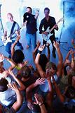 Rock band playing music and young people dancing