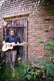rough country guy playing his guitar in the backyard