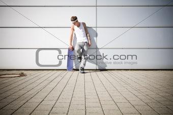 skater holding his skateboard while taking a break