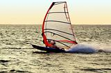 Silhouette of a windsurfer on a gulf, moving at great speed