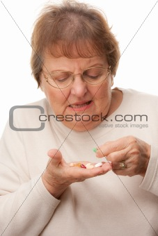 Attractive Senior Woman and Pills Isolated on a White Background.