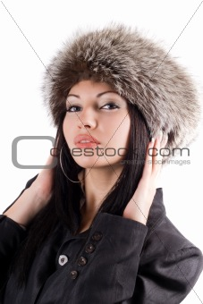 Portrait of the young woman in a fur cap. Isolated
