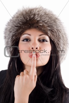 Portrait of the young woman with a finger at lips. Isolated