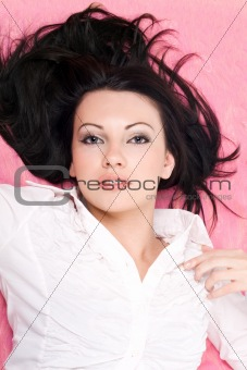 Portrait of the beautiful young woman on a pink background