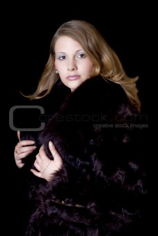 The young beautiful woman in a fur coat