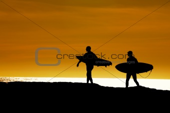 Pair of surfers heading out in the sunset