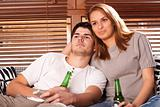 young couple watching tv and drinking beer