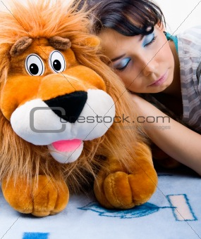 Beautiful sleeping girl with her Plush lion