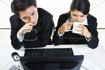 Young Asian businesspeople in office examining monitor