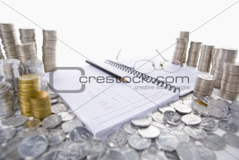Accounting ledger between piles of coins