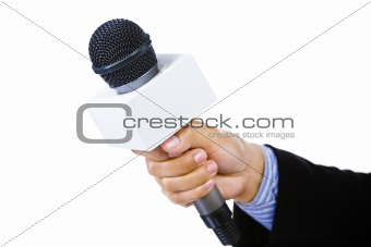 Suited hand holding microphone