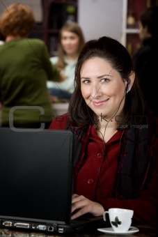 Hispanic woman with earphones and laptop computer