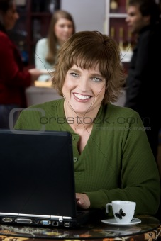 Pretty woman with earphones and laptop computer