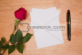 Blank Card, Rose and Pen on a Wood Background.