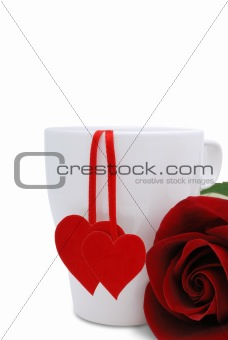 A cup with two red hearts and flower