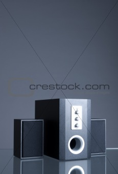 Audio speakers on gray background with reflection