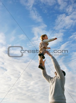father and son playing on sky background