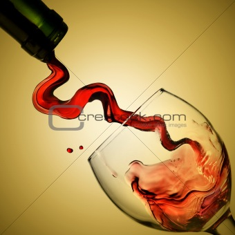 Pouring red wine in goblet on yellow background