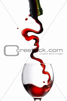 Pouring red wine in goblet isolated on white