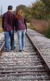 Couple Walking Along Tracks