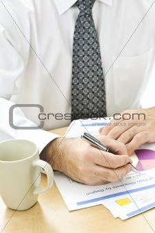 Office worker writing on reports