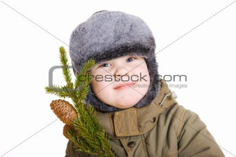 boy in winter coat with a branch of fur tree