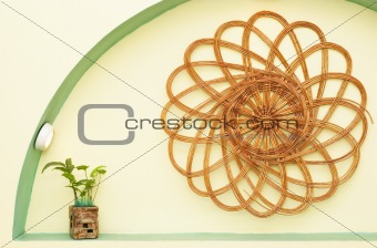 Wattled handicraft and smal green plant in the niche of wall