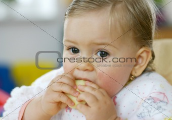Small baby eating apple