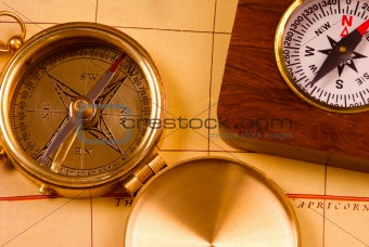 Old style brass compasses on antique map
