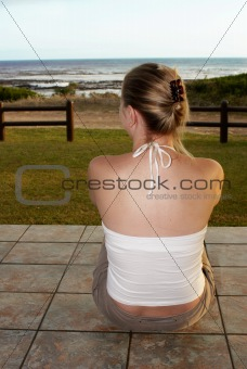 Blonde woman sitting on the tiled floor.