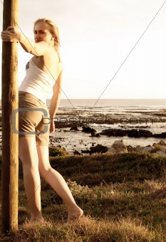 Blonde woman standing outside by the ocean