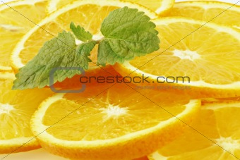 The leaves of mint lying on orange segments.  Orange-green fruit background.