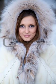 Beautiful young woman in winter fur coat