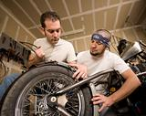 Two Motorcycle Mechanics Placing a Fender