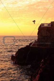 Cliff diver off the coast of Mazatlan at sunset
