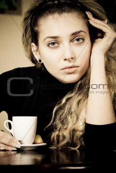 Portrait of beautiful young woman holding a cup of coffee
