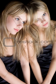 Portrait of the young blonde near a mirror